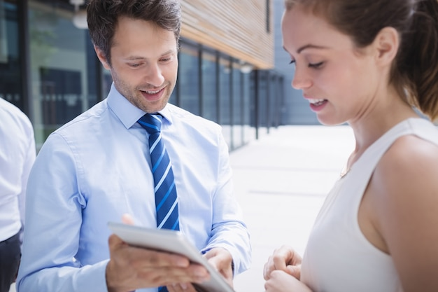 Businessman and colleague discussing over digital tablet