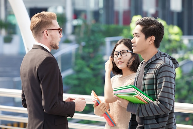 Businessman and college students discussing education