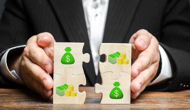 Бизнесмен объединяет денежные пазлы сбор средств с привлечением инвестиций для реализации