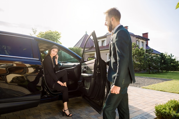 Businessman coming to car and opens door for young woman, talking on the phone. businesswoman get out from the auto and is ready to go with her colleague to office building