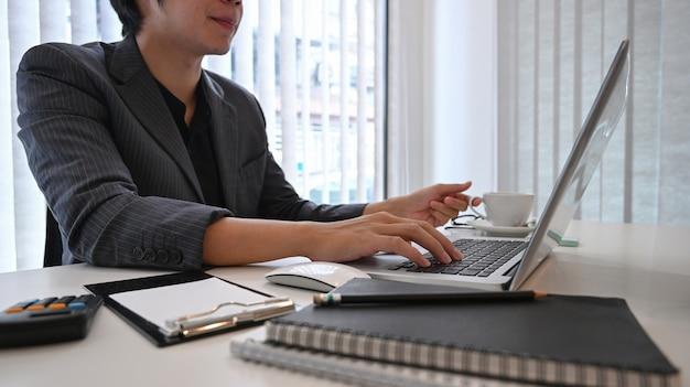 Бизнесмен концентрируется, работая с портативным компьютером в современном офисе.