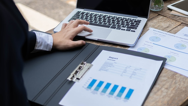 사업가는 노트북을 사용하여 월별 보고서를 작성하기 위한 마케팅 및 판매 데이터를 분석하는 남성 마케팅 회계사를 개념으로 합니다.