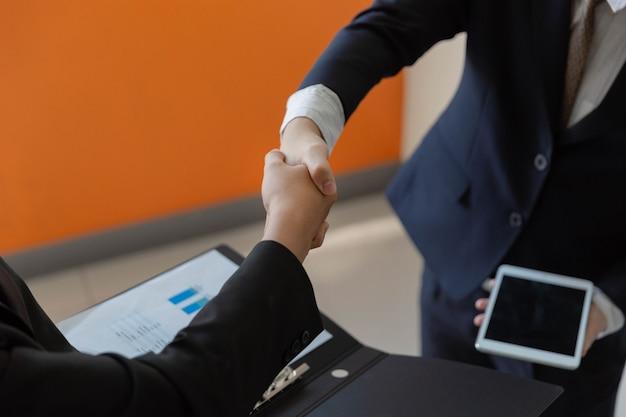 사업가 개념 두 사업가는 계약에 서명한 후 협력하고 악수하기로 합의했습니다.