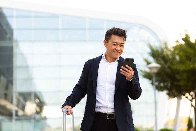 携帯電話で対応するビジネスマンは、メッセンジャーアプリケーションを使用して離れた場所にいる同僚と通信します