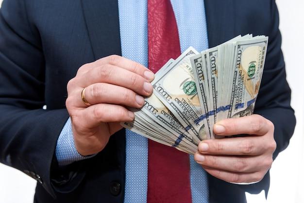 흰 벽에 고립 된 달러 지폐를 계산하는 사업