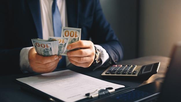 収益金を数えるビジネスマン。金融ビジネスの概念。
