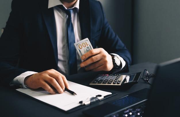 収益金を数えるビジネスマン金融ビジネスの概念