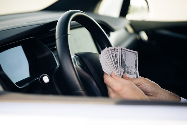Businessman counting money usd bills payday inside car