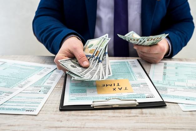 ビジネスマンはドルを数え、us1040の個人税フォームに記入します。碑文税の時間のステッカー。税の概念。