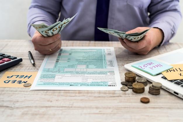ビジネスマンはドルを数え、us1040の個人税フォームに記入します