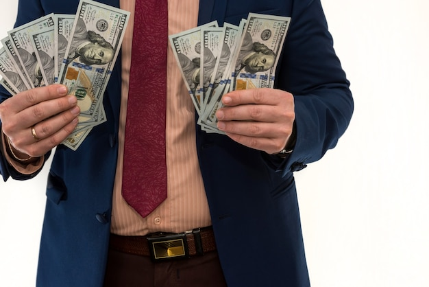 Businessman counts money isolated on white. a man in a suit is making a profit or a win. account of dollars. wealth concept