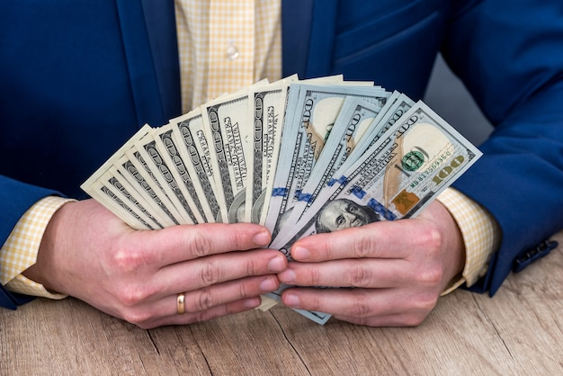 Businessman counts the profit in dollars