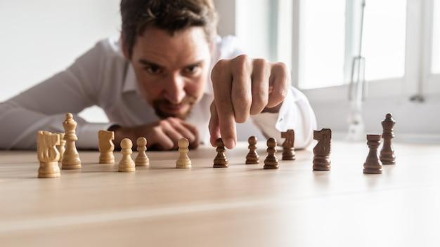 彼のオフィスの机の上に黒と白のチェスの駒を配置することによってビジネス戦略を作成するビジネスマン。