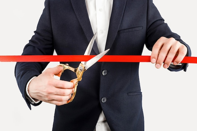 Businessman cutting red ribbon with pair of scissors isolated