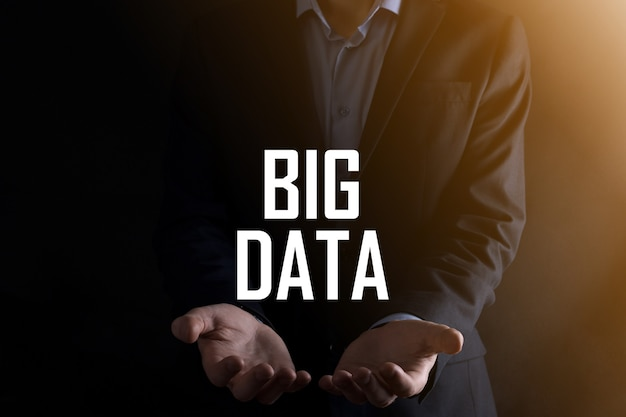 Businessman on a dark background holds the inscription big data.storage network online server