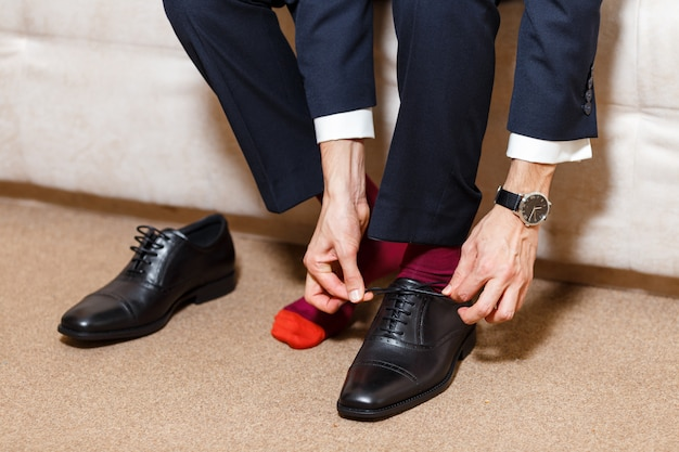 Businessman in dark blue suit, red socks and watch tying his shoelaces of black shoes