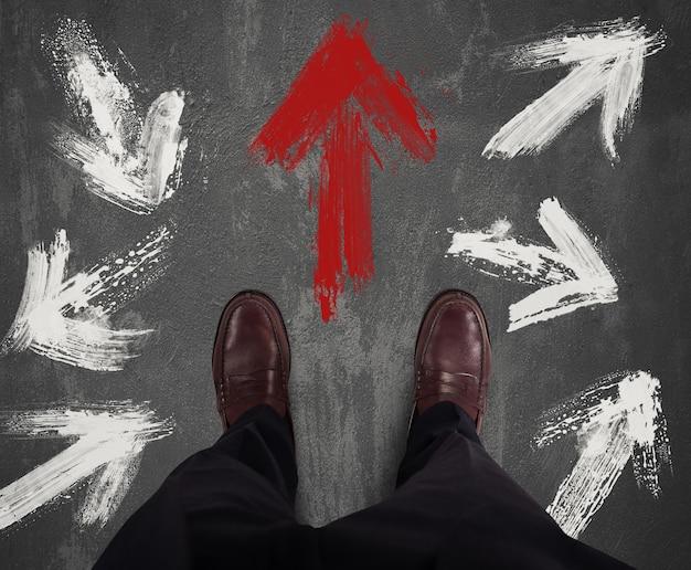 ビジネスマンは方向を決定し、赤い矢印に従います