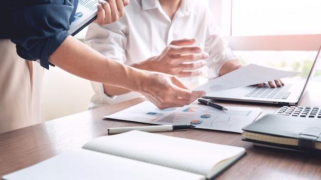 사업가 동료 동료와 함께 문서에 새로운 트렌드 정보를 설명하는 토론