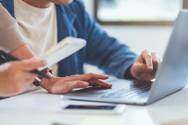 Бизнесмен обсуждает и работает над портативным компьютером вместе в офисе