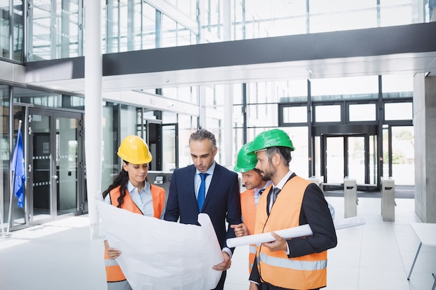 Businessman discussing on blueprint with architects