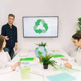 Businessman discussing recycle concept with his female colleague