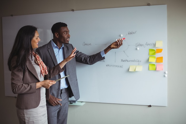 Businessman discussing on white board with a colleague
