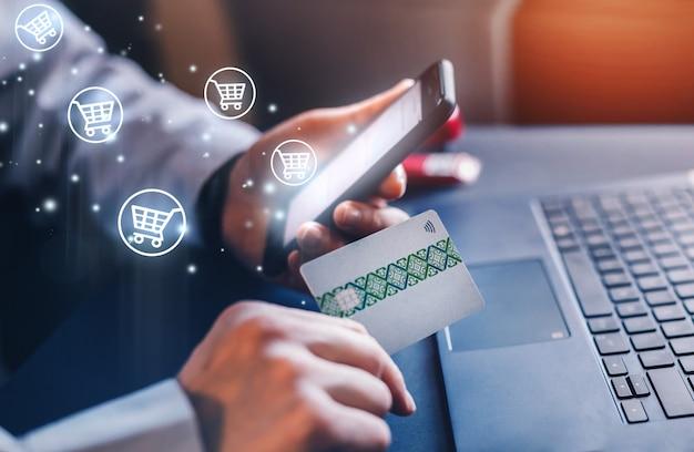 사업가 신용 카드와 휴대 전화로 온라인 쇼핑을합니다.