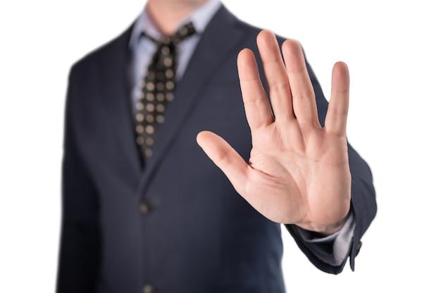 ビジネスマンは白い背景で隔離の彼の手でジェスチャーを停止します