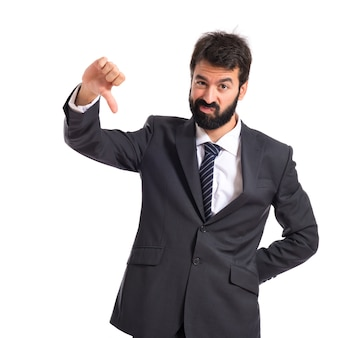 Businessman doing a bad signal over white background