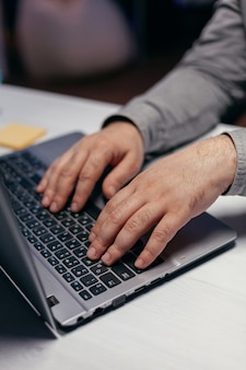 Businessman doing multitasking in dark office. close up of male hands typing on laptop keyboard in office. business, working from home, studying online concept