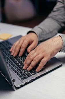 어두운 사무실에서 멀티태스킹을 하는 사업가. 사무실에서 노트북 키보드에 입력하는 남성 손을 닫습니다. 비즈니스, 재택근무, 온라인 개념 공부