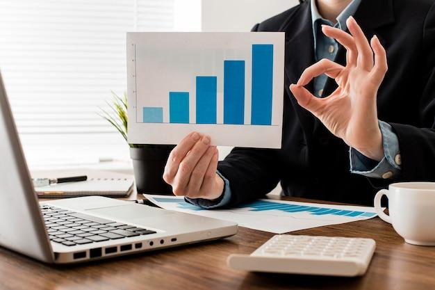 Uomo d'affari che fa il segno giusto mentre si tiene il grafico di crescita