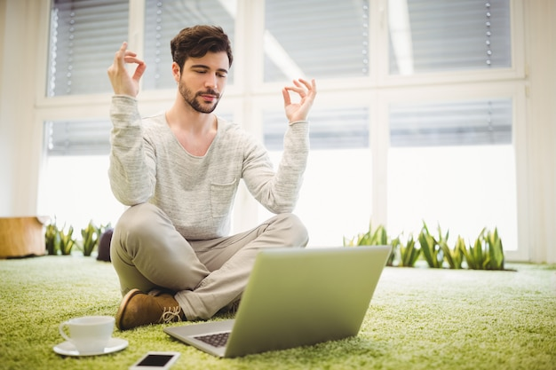 Businessman doing yoga in front of laptop in office