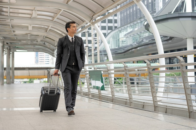 Businessman dragging a suitcase on the bridge