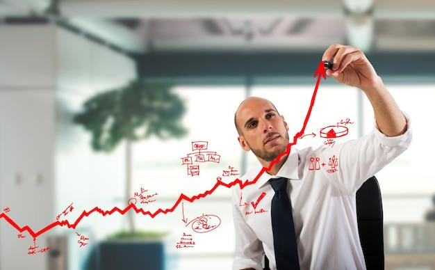 ビジネスマンは上り坂の矢印にグラフィックを描く