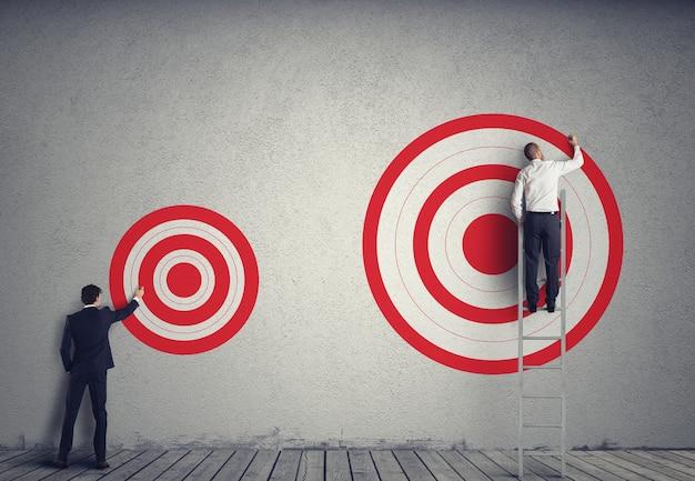 Бизнесмен привлекает более крупную цель своего коллеги. достигайте более важных целей в концепции работы