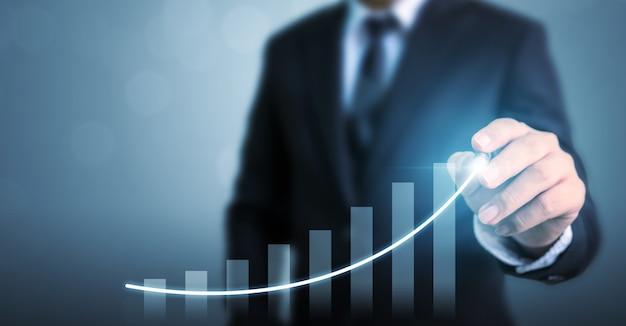 ビジネスマンの矢印グラフ企業の将来の成長計画を描画