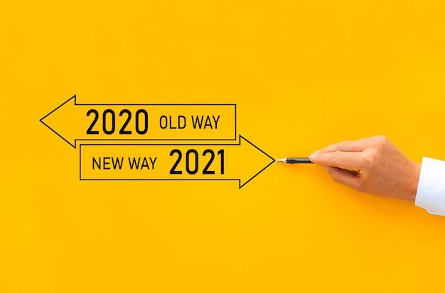 Old way 2020 및 new way of the year 2021으로 화살표 패널을 그리는 사업가. 개선 및 변경 관리.