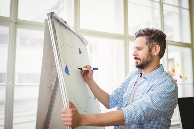Businessman drawing diagram on whiteboard in creative office