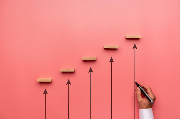 Businessman drawing upwards pointing arrows to support wooden pegs positioned in stairway