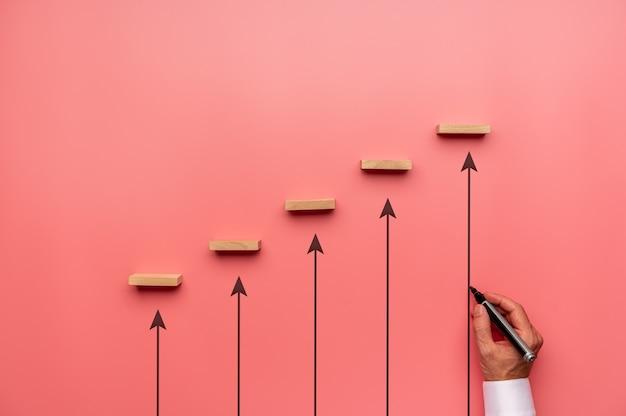Бизнесмен, тянущий вверх, указывая стрелки, чтобы поддержать деревянные колышки, расположенные на лестнице
