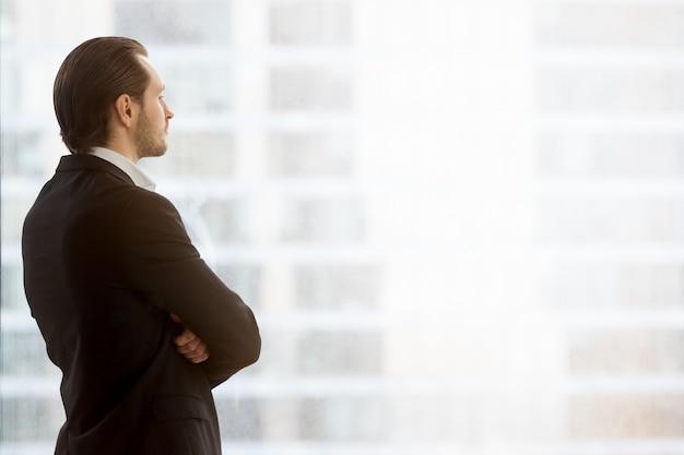 Бизнесмен мечтательно смотрит в окно на офис