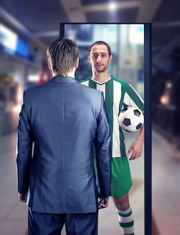 Businessman dreaming to be a football-player stands in front of the mirror