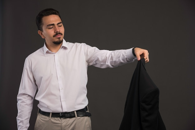 A businessman in dress code holding a black jacket and looking at it.