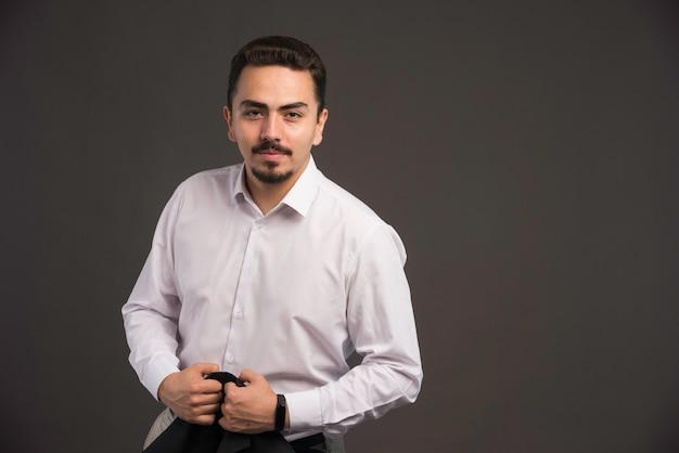 Un uomo d'affari in codice di abbigliamento in possesso di una giacca nera e sorridente.