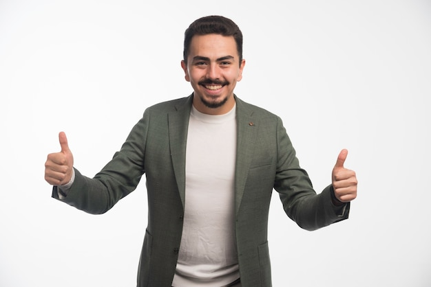 A businessman in dress code makes thumb up.