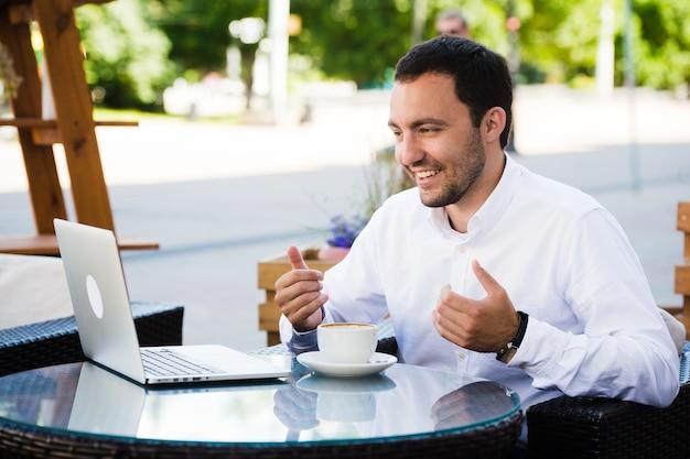 Бизнесмен, одетый в рубашку, делает видеозвонок с ноутбуком в кафе в парке на открытом воздухе