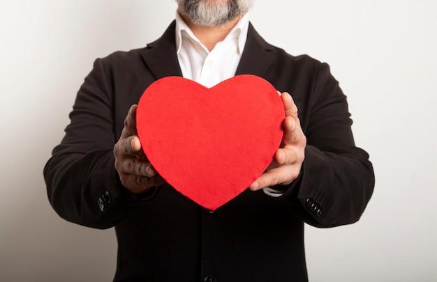 白い背景に赤いハートを保持しているスーツに身を包んだビジネスマン。甘くてロマンチックな瞬間のバレンタインデー。