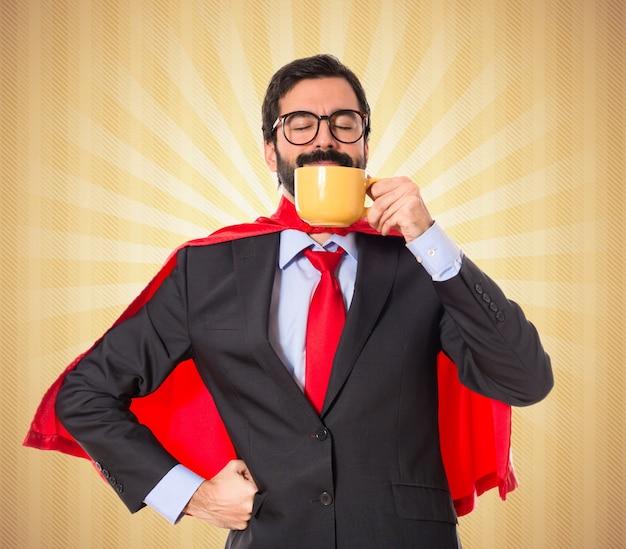 Бизнесмен одет как супергерой пить кофе