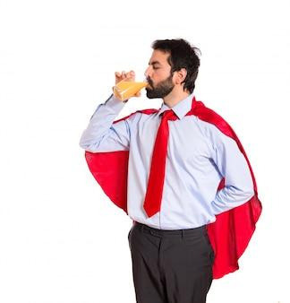 Uomo d'affari vestito come supereroe bere succo d'arancia